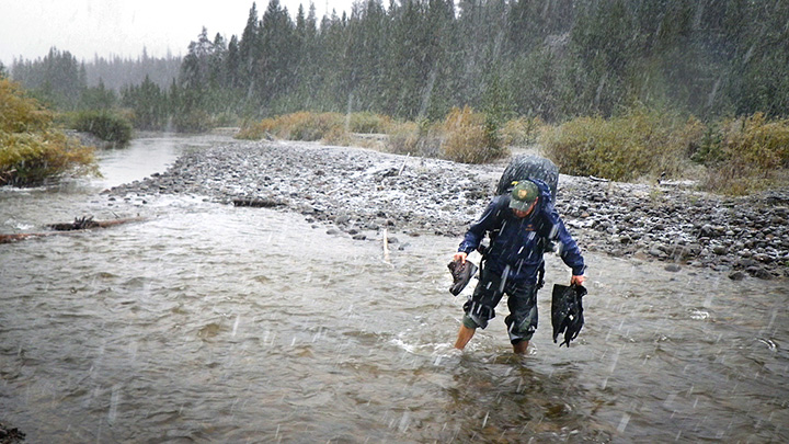 Photo of PLEA student walking through river in the rain.