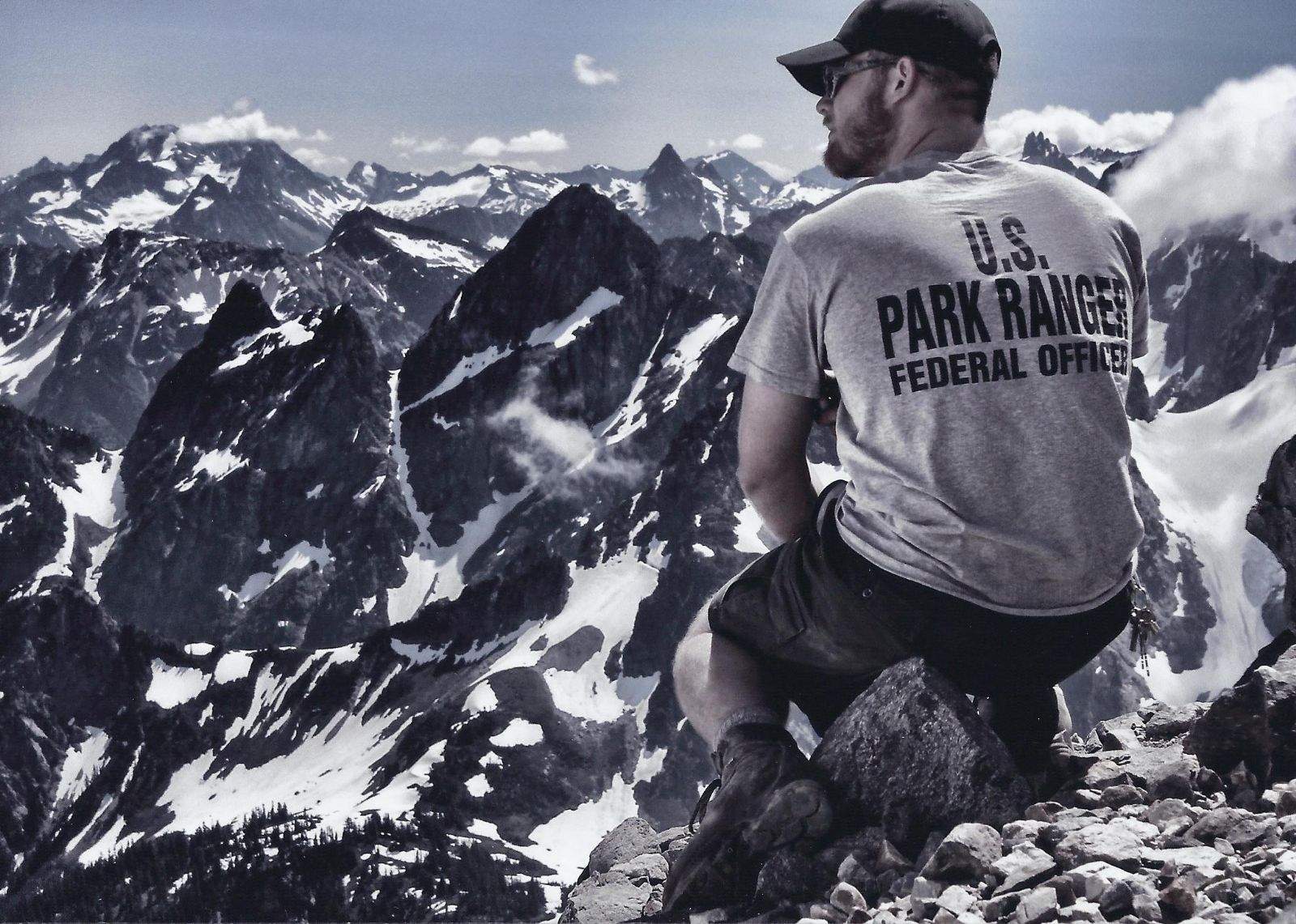 Photo of U.S. Park Ranger perched on mountainside.
